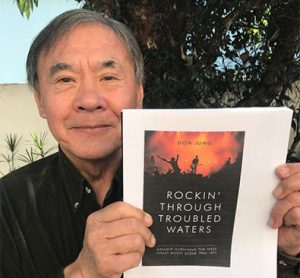 "Don Jung holding his book ""Rockin' Through Troubled Waters"""